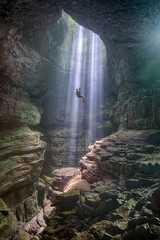 The mist in a dark wet cave is naturally lit by shafts of light coming through an opening in the ceiling.  Using a long rope a man rappels into the mist bathed by sunlight