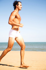 Young shirtless man running on the beach