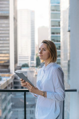 Attractive businesswoman wearing white shirt working on new project of office buildings, manager using modern tablet outside, Tablet on city background, Flare light, Shallow DOF.