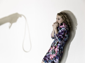 frightened woman standing near the wall with a faceless man holding a belt, a conceptual shoot portraying the process and effects of domestic violence