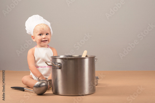 3e2487132a3 Charming and surprised kid in an apron and chef hat sitting next to a big  pot of soup and holding something in his hand