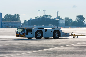 Aircraft tow tractor with moving tug on the airport apron