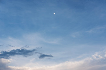 Blue sky and white clouds and moon at dusk