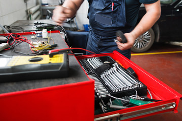 Professional toolbox with modern tools at garage. Mechanic taking facilities from special box for mechanical instruments