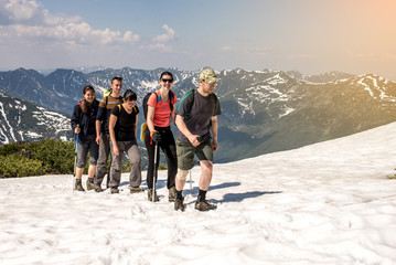 hikers go in groups through the snow
