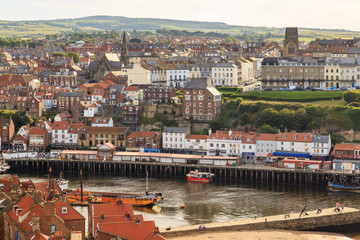 WHITBY, ENGLAND - JULY 16: Whitby harbour, and town behind. In Whitby, North Yorkshire, England. On 16th July 2016.