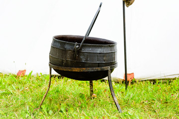 Outdoor iron cooking pot with handle. Cauldron is supported by metal legs.