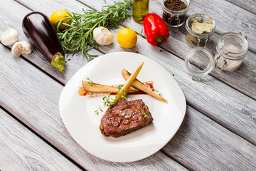 Cooked meat and raw vegetables. Eggplant and rosemary. Ribeye steak with thyme. Tasty food cooked at bistro.