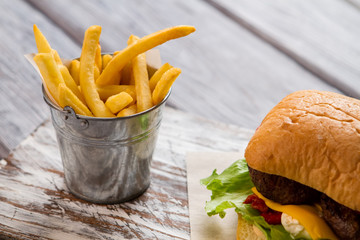 Bucket with fries and burger. Grilled meat and bun. American meal in cafe. Best recipe of beefburger.
