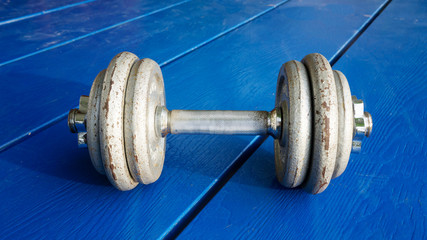 Iron dumbbell on a blue wooden deck.