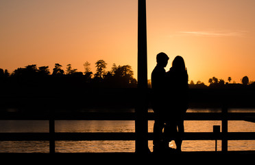 Romantic couple on a pier in Santa Cruz hugging during sunset