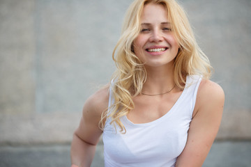 Young blonde model with long hair in white tank top