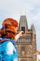 Young girl tourist taking a picture of Prague city. Back focus