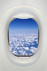Window of an airplane from inside, view on snowy mountains (the Alps)