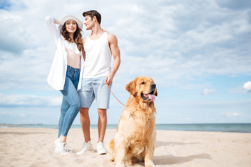 Couple and their dog standing on the beach