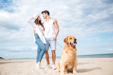 Dog sitting in front of couple standing on the beach