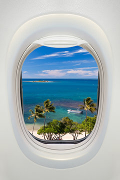 Window of an airplane from inside, view on a tropical beach and sea