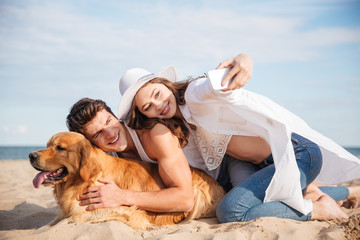 Couple with dog talking selfie using smartphone on the beach