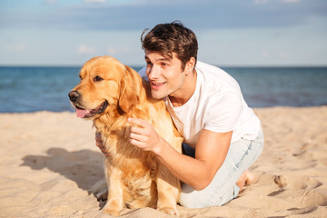 Man hugging and talking with dog on the beach