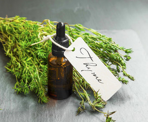 Thyme oil bottle with label and thyme bunch