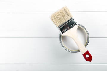 paint can with paintbrush on white wooden background with copysp