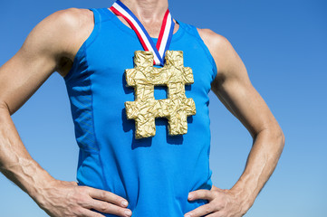 American athlete with gold medal hashtag hanging from USA colors red, white, and blue ribbon standing against bright blue sky