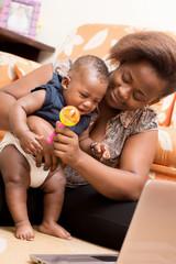 mère heureuse assise devant un ordinateur portable et jouant avec son bébé