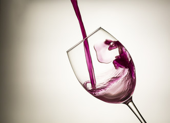 Red wine pouring in a wineglass