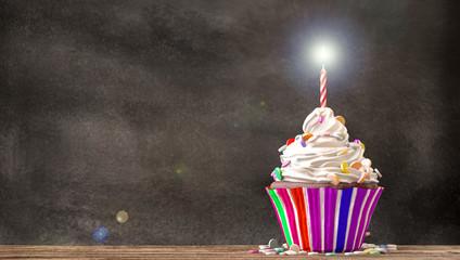 Cupcake à la crème, bonbons et une bougie sur une table en bois sur fond de tableau noir. Espace libre  disponible. Rendu 3D