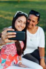 Mother and daughter women using a mobile phone