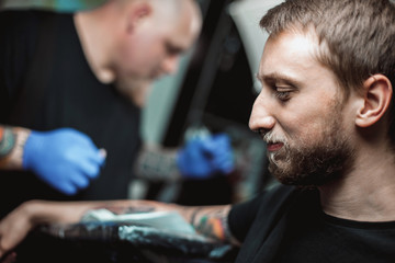 master tattooist makes a tattoo on the skin of the client in a workshop with special equipment