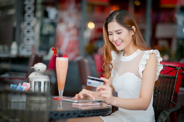 Woman buying online on vacations with a laptop and a credit card