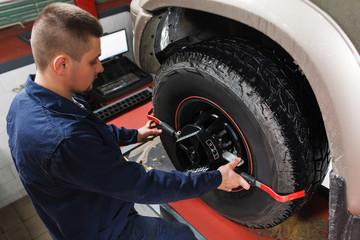 Mechanic tuning aligner for wheel alignment in garage closeup. Professional car maintenance in modern workshop