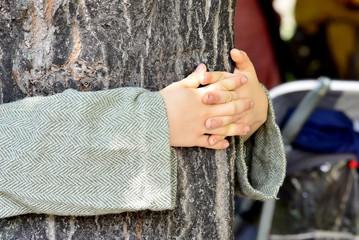 Kinderhände beim Umarmen eines Baumes