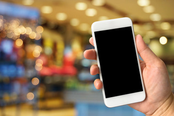 Woman hand holding smartphone against blur bokeh of shop backgro