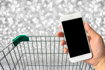 Woman hand holding smartphone against blur bokeh with shopping c