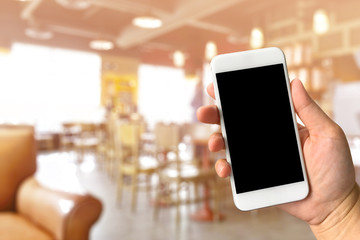 Woman hand holding smartphone against blur bokeh of coffee shop