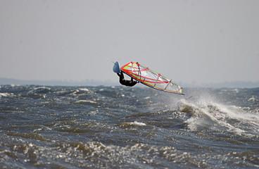 windsurfer bei Sturm macht einen hohen Luftsprung