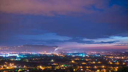 The beautiful night view on the city against the background of cloud stream. Wide angle