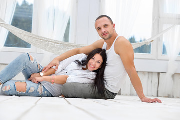 Happy couple sitting on the floor at home