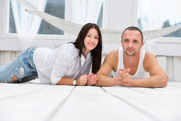 Happy couple lying on the floor at home