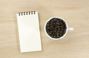 paper note with coffee bean in whith cup on wooden