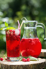 Homemade berry juice in a glass and jug with raspberry redcurrant in summer garden