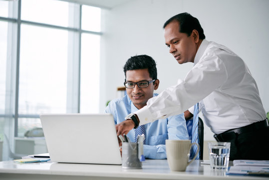 Indian business team discussing information on tablet computer