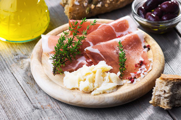Thin slices of prosciutto with  pecorino on wooden background