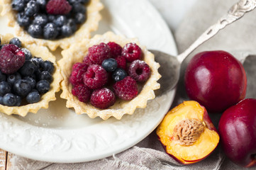 baskets of pastry with fresh berries on plate.