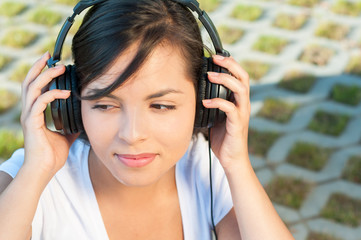 Girl holding headphones and listening to music