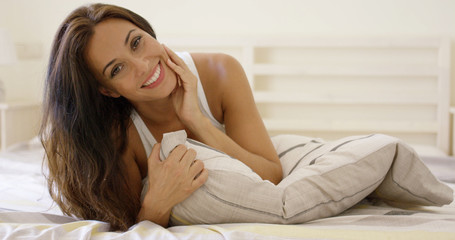Happy young woman cuddling up in bed hugging the pillow to her chest as she grins at the camera with a friendly smile