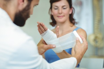 Physiotherapist putting bandage on injured hand of patient