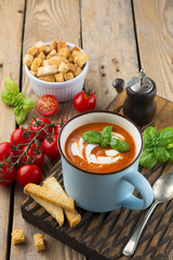 Tomato soup in a ceramic cup on the old wooden background. Selective focus.